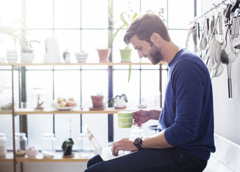 Young man sitting on kitchen counter with mug and laptop - CAIF13300
