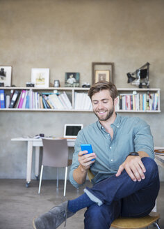 Young blonde man sitting with mobile phone in studio - CAIF13306