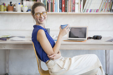 Young woman sitting with mug in home office - CAIF13309