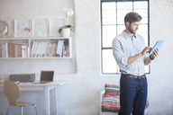 Man with digital tablet standing in home office - CAIF13318