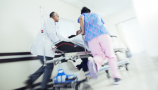 Doctor and nurse rushing patient on stretcher in hospital corridor - CAIF13339
