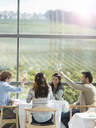 Friends toasting wine glasses in winery dining room - CAIF13360
