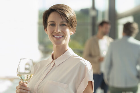 Portrait smiling woman drinking white wine - CAIF13372