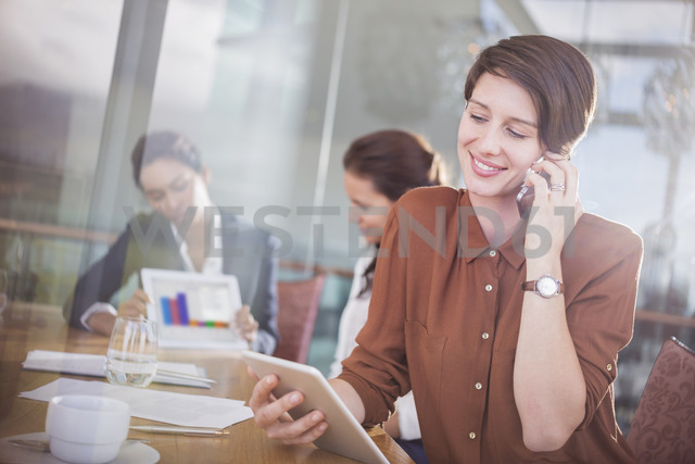 Businesswoman talking on cell phone and using digital tablet in office - CAIF13390