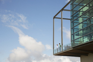 Men talking on balcony of glass bump out against blue sky - CAIF13405