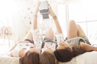 Three teenage girls taking selfie while lying on bed in bedroom - CAIF13417
