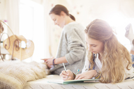 Two teenage girls on bed writting in notepads - CAIF13420