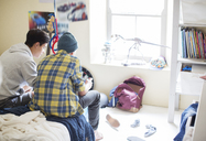 Two teenage boys sitting on bed in messy room - CAIF13435