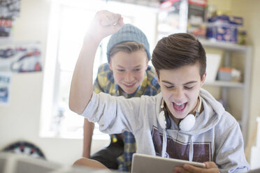 Two teenage boys having fun while using digital tablet - CAIF13447