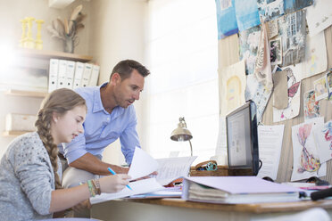 Father helping teenage daughter with her homework - CAIF13456