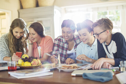 Group of teenagers using electronic devices at table in dining room - CAIF13471