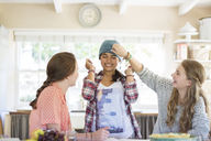 Three teenage girls playing with beanie in dining room - CAIF13477