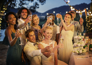 Wedding guests toasting with champagne during wedding reception in garden - CAIF13486