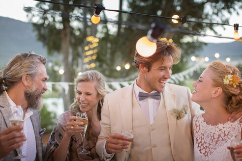 Young couple and their guests with champagne flutes during wedding reception in garden - CAIF13492