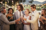 Young couple and their guests with champagne flutes during wedding reception in garden - CAIF13495