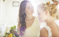 Bridesmaid helping bride with hairstyle in bedroom - CAIF13501