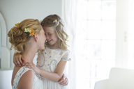 Bride and bridesmaid facing each other and smiling in bedroom - CAIF13507