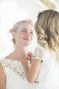 Bride and bridesmaid facing each other and smiling - CAIF13519