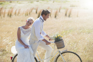 Young couple riding bike in meadow - CAIF13525