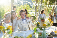 Young couple and bridesmaid during wedding reception in domestic garden - CAIF13546