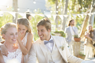 Bridesmaid whispering to bride's ear during wedding reception in domestic garden - CAIF13552