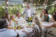 Best man speaking during wedding reception in domestic garden - CAIF13555