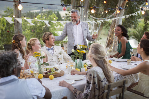 Best man speaking during wedding reception in domestic garden - CAIF13555