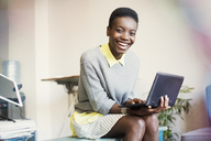 Portrait smiling businesswoman working with digital tablet - CAIF13558