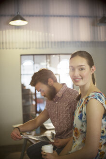 Portrait smiling casual businesswoman reviewing proofs with businessman in office - CAIF13600