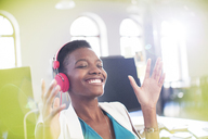 Smiling businesswoman listening to music on headphones in office with eyes closed - CAIF13606