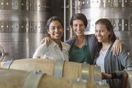 Portrait smiling women in winery cellar - CAIF13621