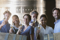Portrait smiling friends wine tasting in winery cellar - CAIF13624