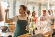 Wine tasting room worker examining white wine - CAIF13630