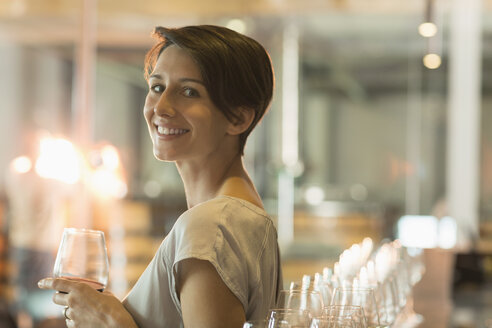 Portrait smiling woman wine tasting at winery tasting room - CAIF13651
