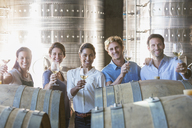 Portrait smiling winery employees barrel tasting in cellar - CAIF13669