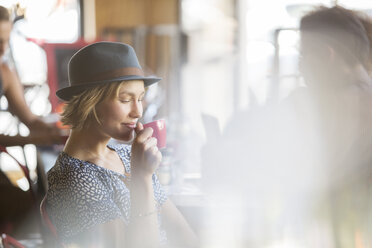 Woman in hat drinking coffee in cafe - CAIF13720