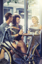 Friends hanging out at cafe table behind bicycle - CAIF13723