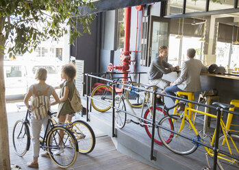 People with bicycles at urban outdoor cafe - CAIF13729
