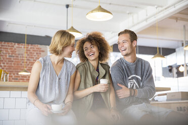 Laughing friends drinking coffee in cafe - CAIF13735