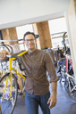 Portrait smiling man with eyeglasses carrying bicycle in bicycle shop - CAIF13738
