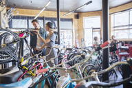 Couple browsing bicycles on rack in bicycle shop - CAIF13747