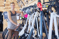 Portrait smiling young man leaning on rack in bicycle shop - CAIF13750