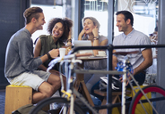 Friends hanging out in cafe behind bicycle - CAIF13753