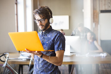 Casual businessman wearing headphones and using laptop in office - CAIF13840