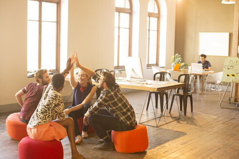 Casual business people joining hands in meeting in office - CAIF13873