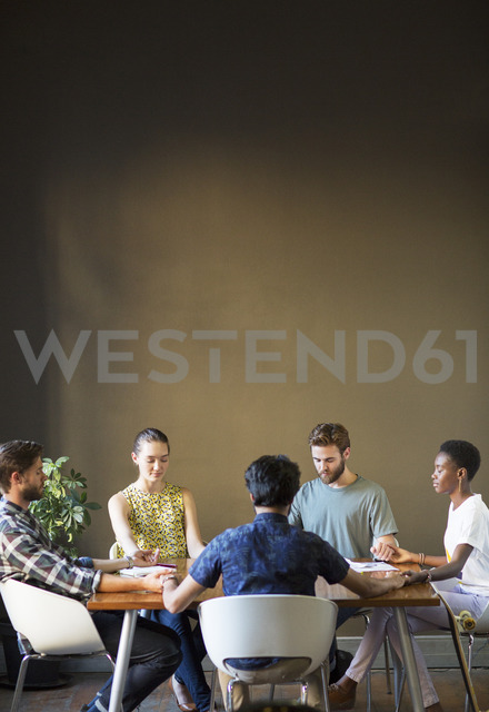 Serene casual business people holding hands with eyes closed at office table - CAIF13900