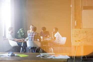 Lens flare over creative business people meeting at office table - CAIF13903
