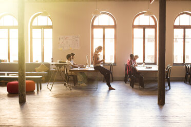 Creative business people working in sunny open office - CAIF13906