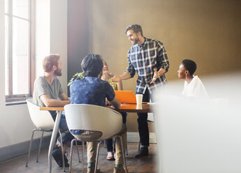 Casual businessman leading meeting at table in office - CAIF13912