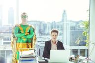 Superhero standing near businesswoman working in office - CAIF13930